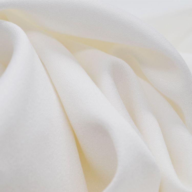 现货供应米白色人棉贡缎面料 时尚缎纹风格 柔软舒适童装女装布料